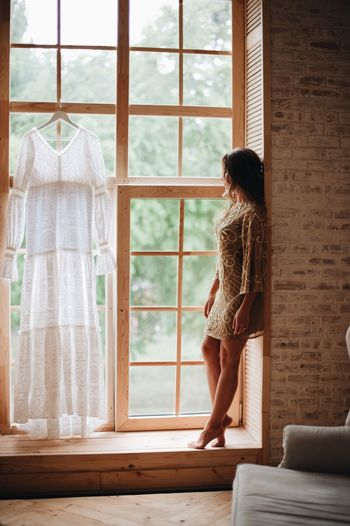 Full Length Of Woman Looking Through Window At Home