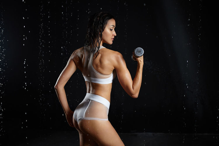Woman exercising with dumbbell against black background