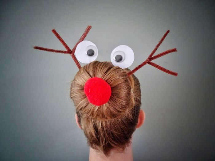 Rear view of woman wearing decoration on hair bun against wall