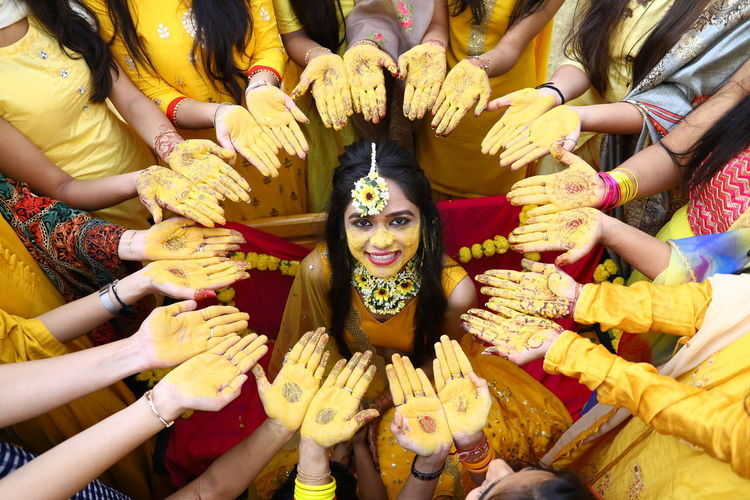 Portrait of smiling bride surrounded with females showing henna tattoo at haldi ceremony