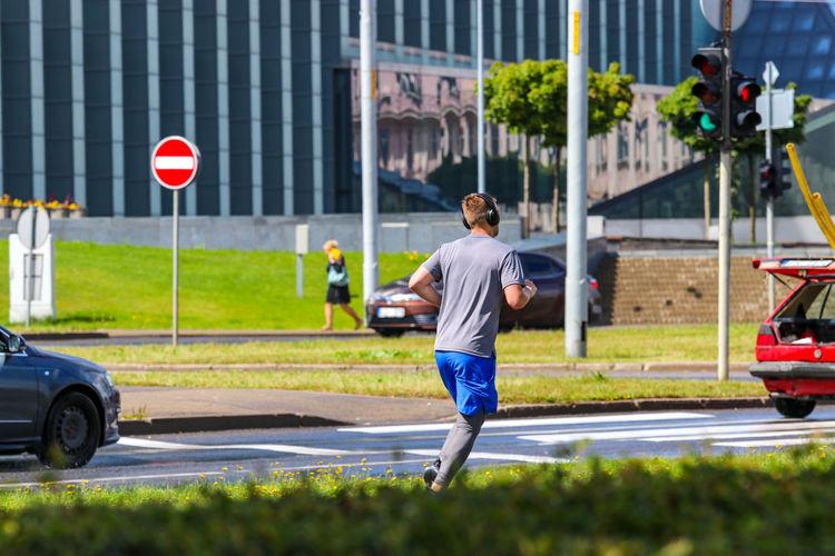 Rear view of boy walking on street in city