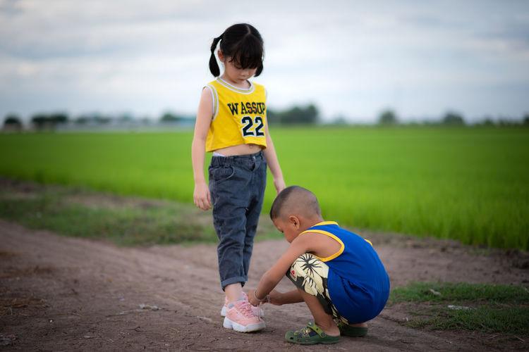 Full length of children on field