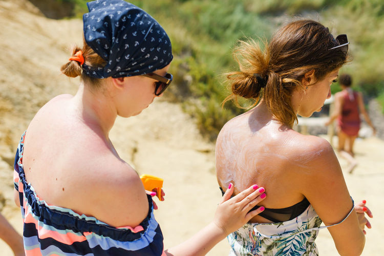 Woman applying lotion to friend at beach