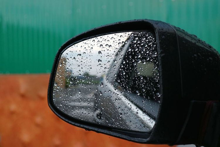 Close-up of raindrops on side-view mirror