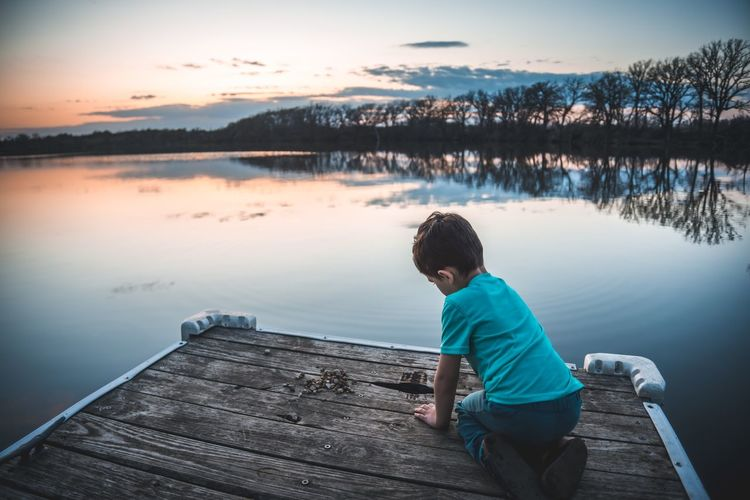Boy On Jetty Over Lake Against Sky During Sunset