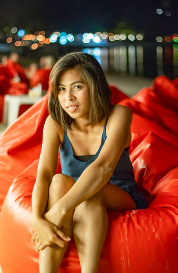 Asian woman sitting on Bean bag Background ocean and lights at night. Hairstyle Clothing Beauty Beautiful Woman Adult Indoors  Young Women Leisure Activity Women Portrait Real People Young Adult Sitting Three Quarter Length Front View Looking At Camera Red Lifestyles One Person Indoors  Smiling