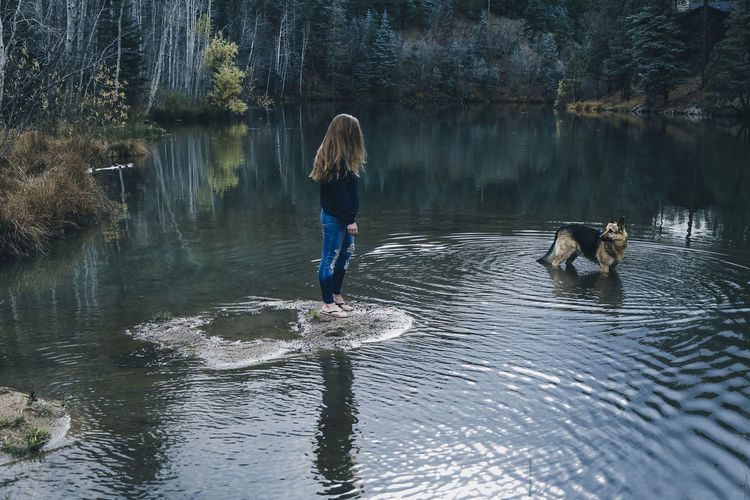 A woman stands on the edge of a mountain lake with her dog Arizona Jeans Natural Light Pond Reflection Standing Storm Woman Beauty In Nature Day Dog Forest Full Length German Shepherd Kerry Estey Keith Lake Long Hair Mountains Nature One Person Outdoors Sky Tree Water Young Woman