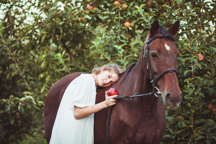 Portrait of woman holding apple standing by horse