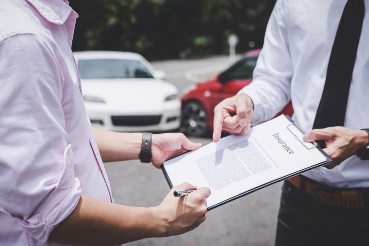 Midsection of man signing insurance paper held by agent at parking lot