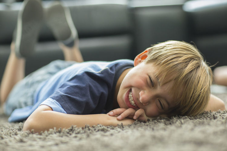 Portrait Of Smiling Boy Lying Down On Carpet At Home