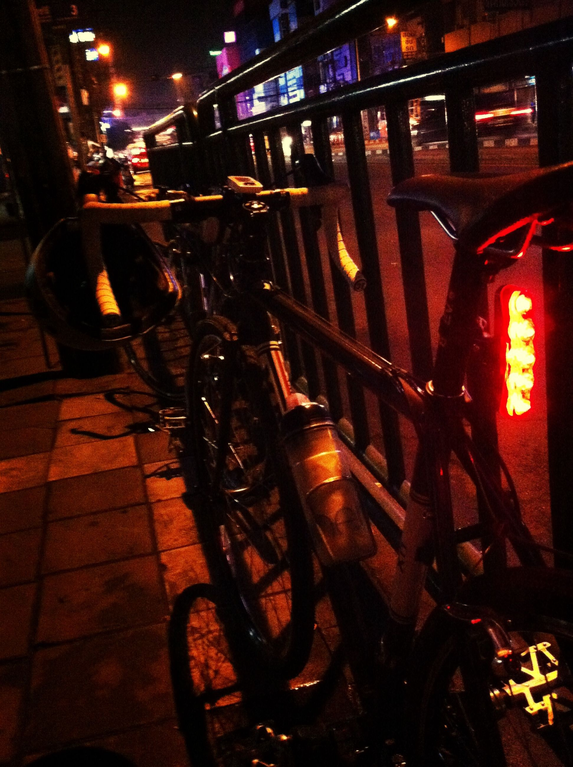 bicycle, night, transportation, illuminated, land vehicle, mode of transport, street, architecture, built structure, parking, city, building exterior, city life, parked, men, shadow, road, stationary, high angle view