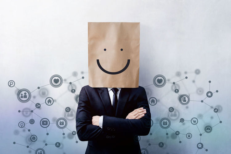 Digital composite image of businessman wearing paper bag with anthropomorphic face