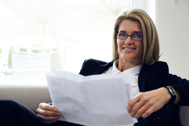 Portrait Of Confident Businesswoman Holding Documents While Sitting On Sofa