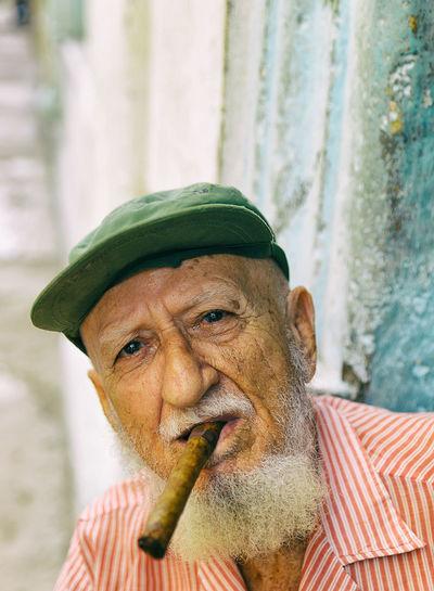 Portrait of senior man wearing cap smoking cigar