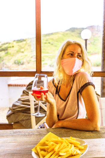 Smiling woman wearing mask holding wineglass sitting at restaurant