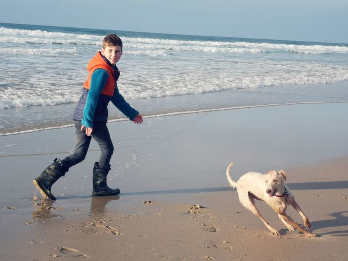 a boy and a dog Sandy Beach Autumn Boy And Dog Running On Beach Bedlington Whippet Warm Clothes Cornwall EyeEm Nature Lover EyeEm ready Pets Sea Full Length Beach Dog Sand Sports Clothing Standing Happiness Walking Rushing Low Tide Human Connection