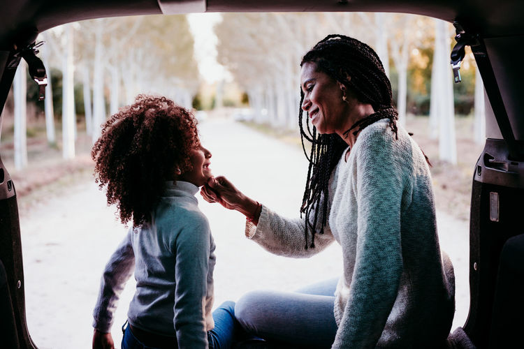 Smiling mother sitting with daughter in car trunk
