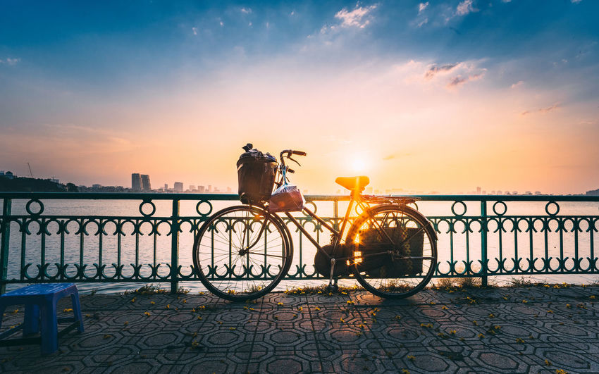 Bicycle by railing by water during sunset