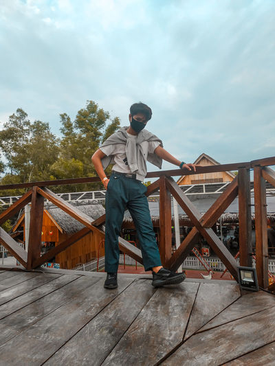 Full length of man wearing mask standing by railing against sky