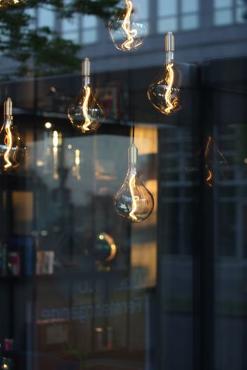Close-up of illuminated light bulbs hanging from glass window