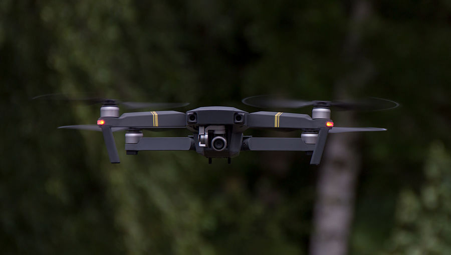 Close-up of drone flying against trees