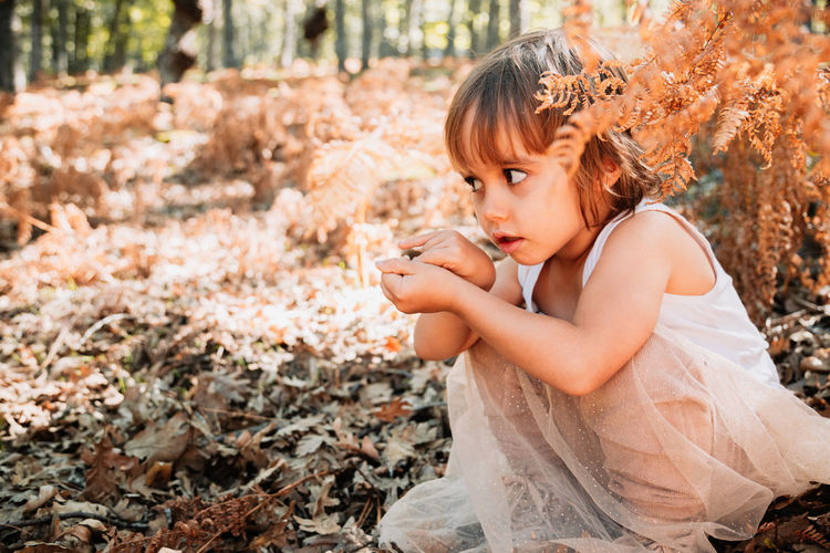 Side view of girl crouching amidst plants on field