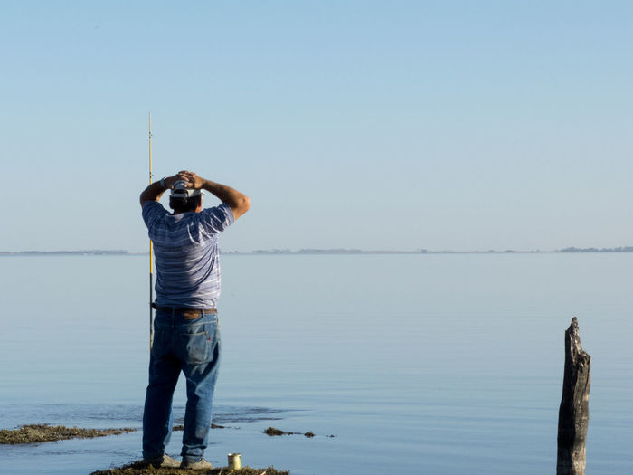 Man fishing in sea against clear blue sky