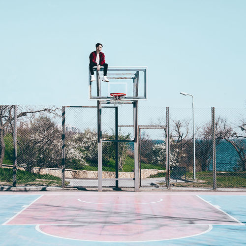 Man sitting on basketball hoop against sky
