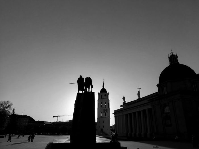 Silhouette of statues on building against sky