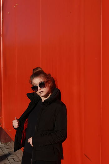 Portrait of young woman standing against red wall