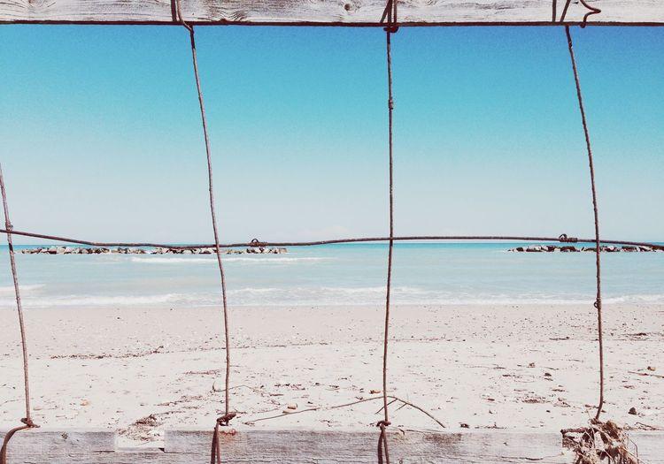 View of beach through fence