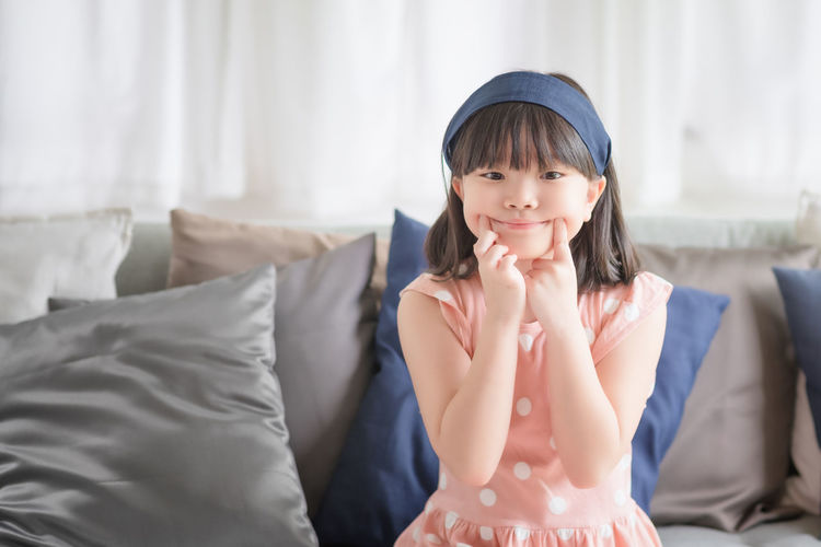 Portrait of a smiling girl sitting at home