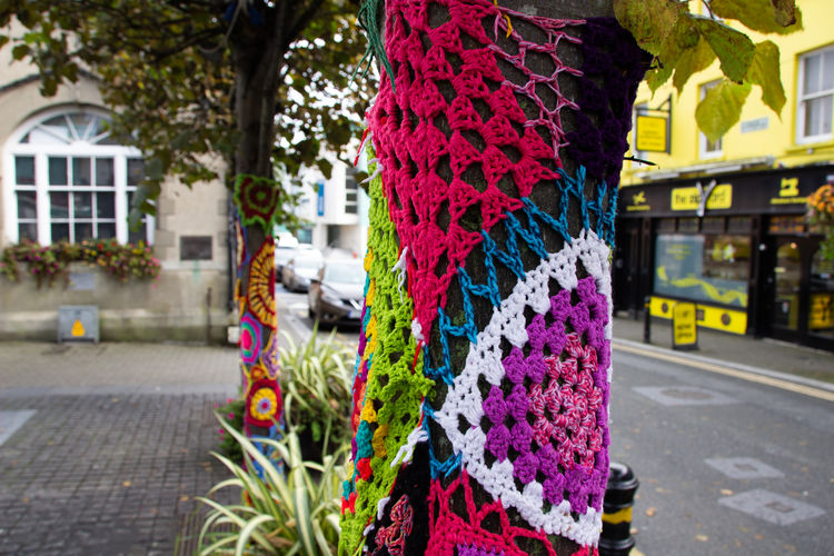 Close-up of multi colored umbrellas hanging on street in city