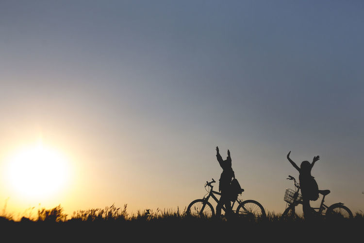 Silhouette of bicycle on field against sky at sunset