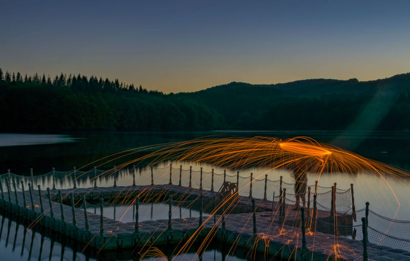 Man spinning wire wool on pier in lake against clear sky at sunset
