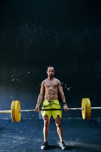 Full length of shirtless man sitting on wall