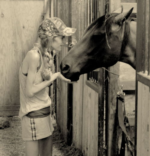 Young woman standing by horse in stable