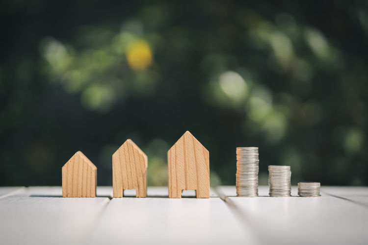 Close-Up Of Wooden Model Homes And Stacked Coins On Table