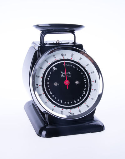 Close-up of old-fashioned weighing scale against white background