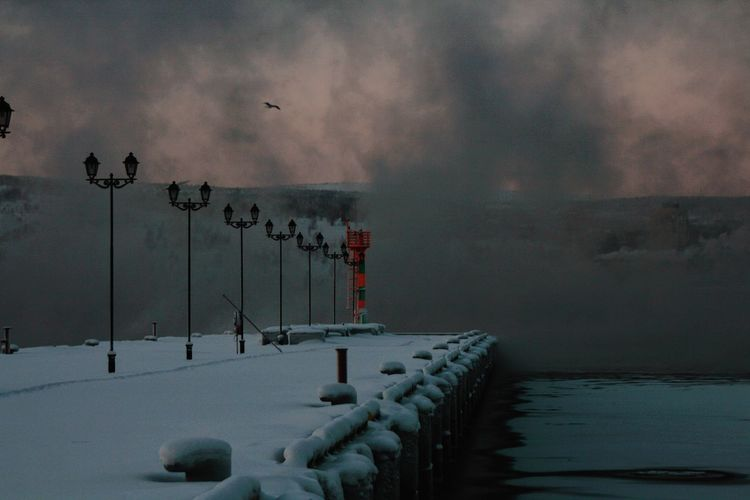 Snow covered pier on sea against cloudy sky at dusk