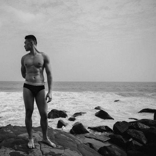 Full length of shirtless man standing on beach against sky