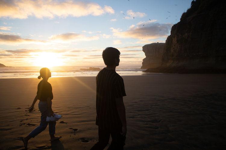 Men on beach against sky during sunset