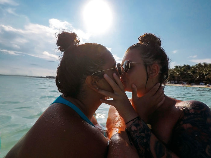 Side view of couple kissing in sea