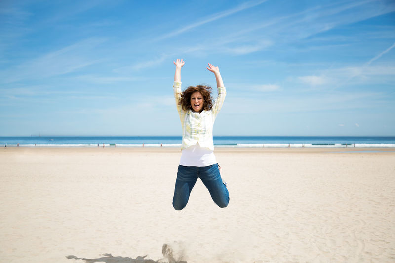 Full Length Of Woman Jumping In Mid-Air At Beach Against Sky