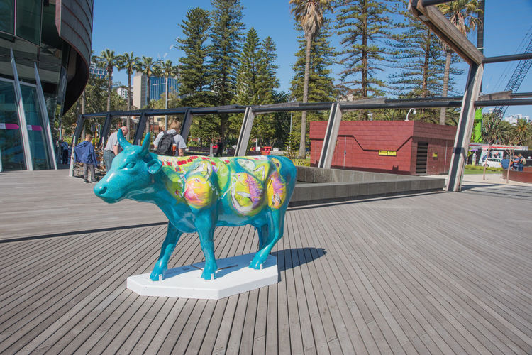 November 16,2016: Vibrant bull art installation outside the Swan Bell Tower with tourists in Perth, Western Australia. Animal Representation Architecture Art Art Installation Artistic ArtWork Australia Blue Building Exterior Built Structure Bull City Cow Creativity Custom Multi Colored Outdoors Painted Perth Sculpture Sky Swan Bell Tower Tourists Turquoise Western Australia