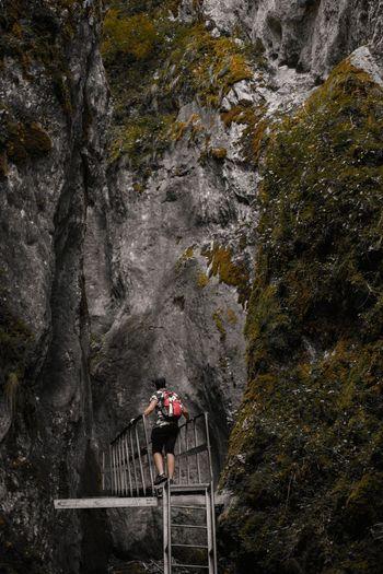 Man on footbridge in the mountains