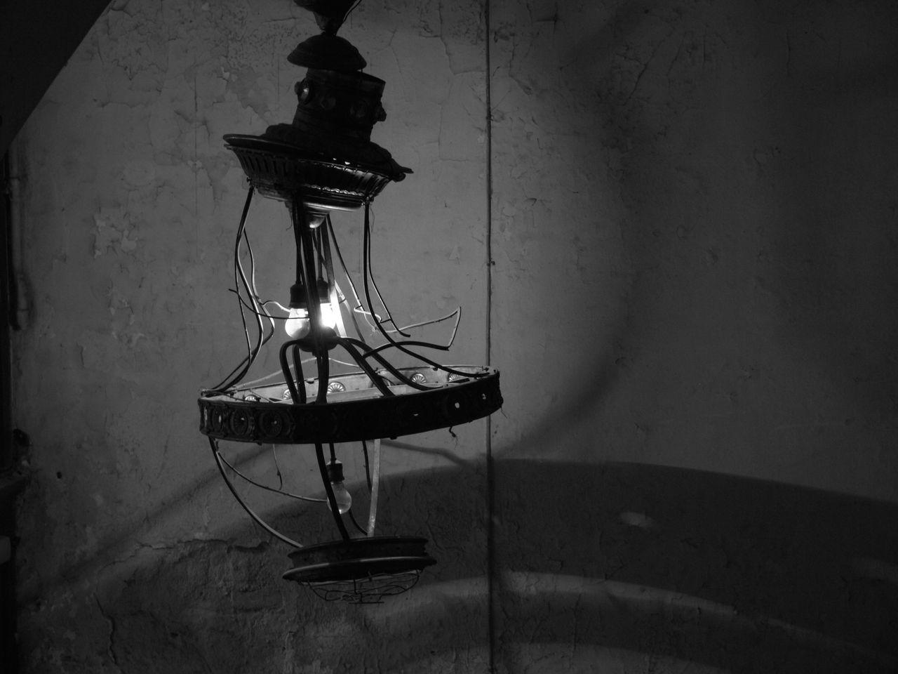 Damaged Illuminated Light Bulb Against Wall