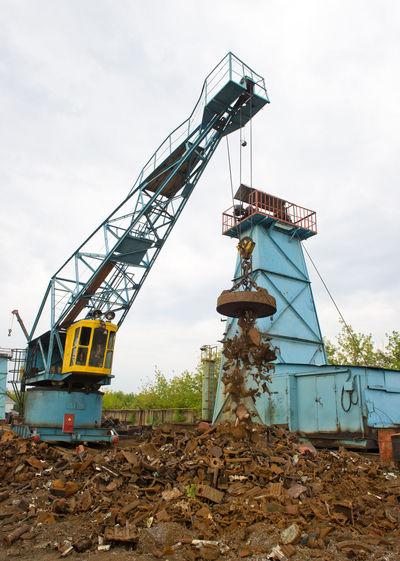 Crane At Metallic Junkyard Against Sky