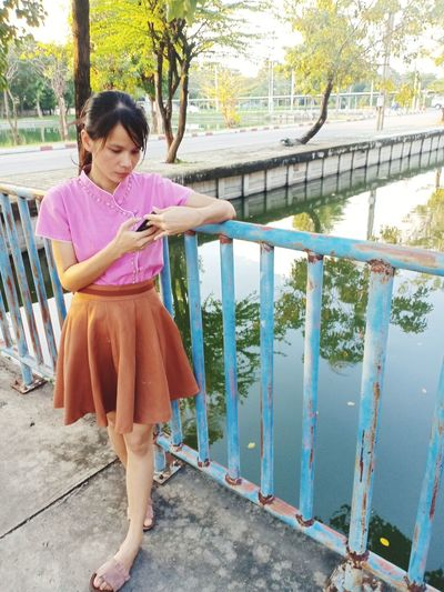 Woman using phone while standing by railing