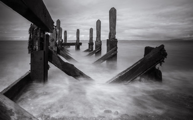 Damaged pier over sea against sky